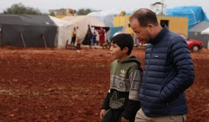 Zaher Sahloul, MedGlobal President, speaking with a child in the IDP camps of Northwest Syria.