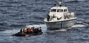 A Hellenic coast guard rescues refugees and migrants on a dinghy as they try to reach the Greek island of Lesbos while crossing the Aegean sea from Turkey