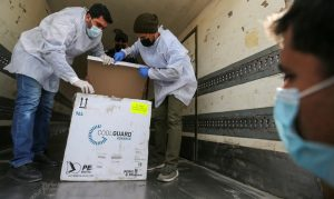 Palestinian workers unload the first shipment of coronavirus disease (COVID-19) vaccines, in the southern Gaza Strip February February 17, 2021.
